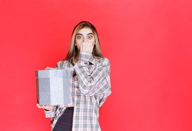 Mujer joven en camisa a cuadros sosteniendo una caja de regalo plateada y parece aterrorizada y asustada
