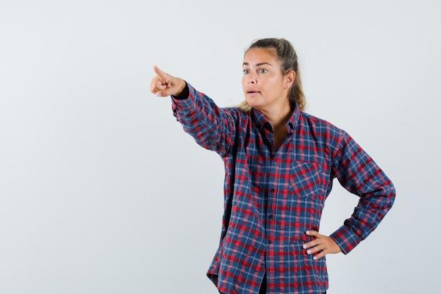 Mujer joven en camisa a cuadros sosteniendo la mano en la cintura mientras apunta a la izquierda con el dedo índice y mira enfocado