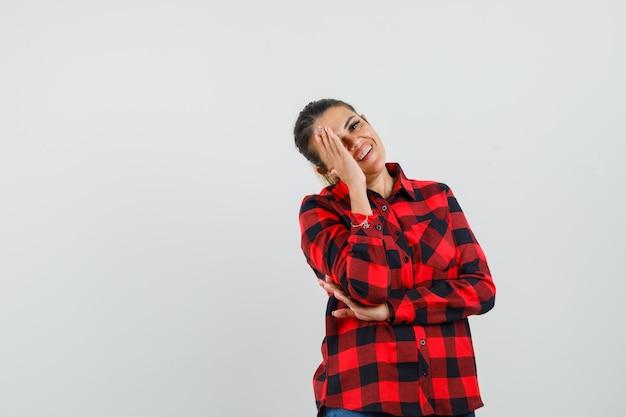 Mujer joven en camisa de cuadros sosteniendo la mano sobre la cara mientras se ríe, vista frontal.