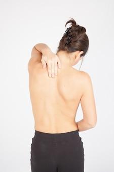 Mujer joven sin camisa con dolor de espalda