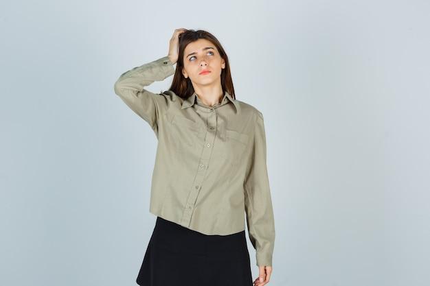 Mujer joven en camisa, falda manteniendo la mano en la cabeza y mirando pensativo