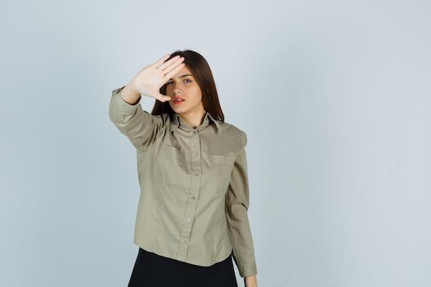 Mujer joven en camisa, falda mostrando gesto de parada y mirando molesto, vista frontal.