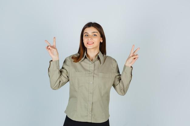 Mujer joven en camisa, falda mostrando gesto de paz y mirando alegre, vista frontal.