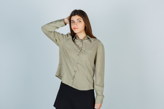 Mujer joven en camisa, falda rascándose la cabeza mientras curva los labios y mira pensativa