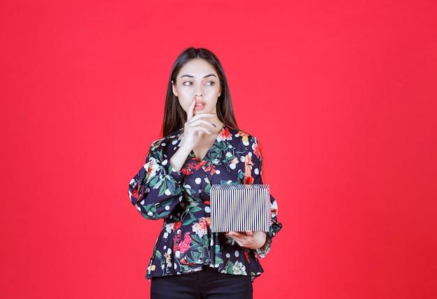 Mujer joven en camisa floral sosteniendo una caja de regalo plateada y parece pensativa