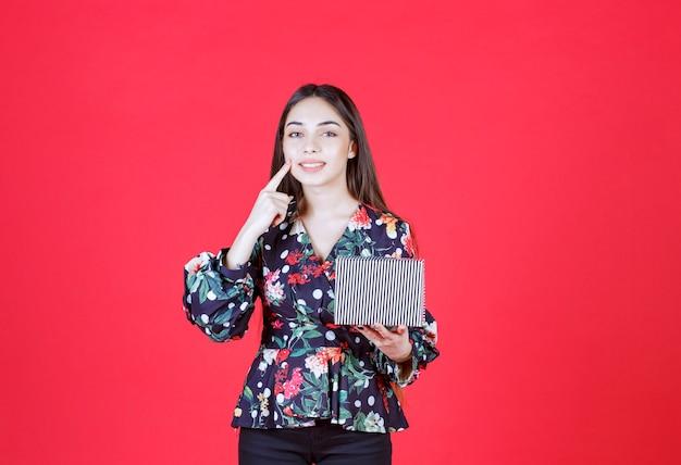 Mujer joven en camisa floral sosteniendo una caja de regalo plateada
