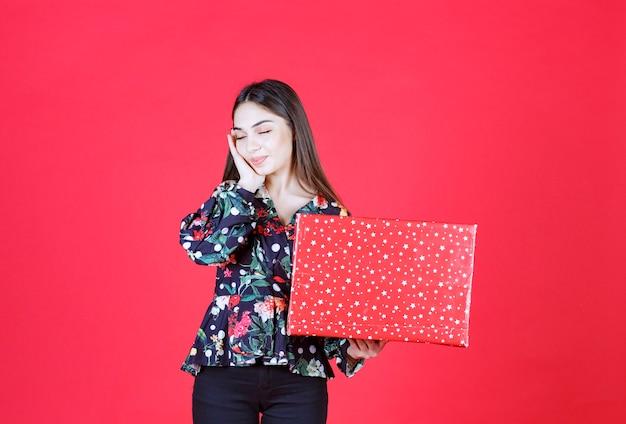 Mujer joven en camisa floral sosteniendo una caja de regalo roja con puntos blancos y parece confundida y pensativa