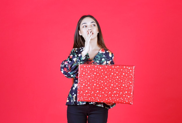 Mujer joven en camisa floral sosteniendo una caja de regalo roja con puntos blancos, poniendo la mano a la boca y llamando a alguien