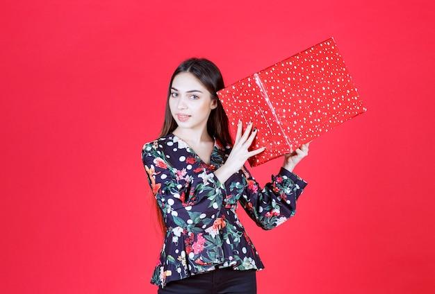 Mujer joven en camisa floral sosteniendo una caja de regalo roja con puntos blancos en él