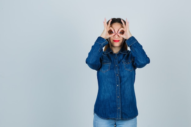 Mujer joven en camisa de mezclilla y jeans mostrando gesto de gafas y mirando lindo