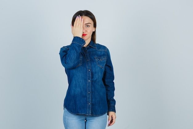 Mujer joven en camisa de mezclilla y jeans sosteniendo la mano en el ojo y mirando lindo