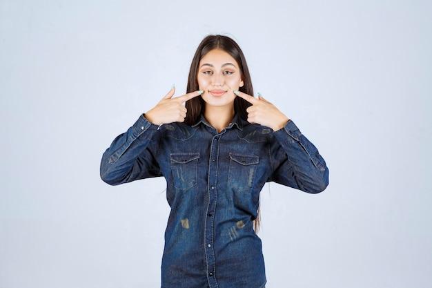 Mujer joven en camisa de mezclilla sonriendo y haciendo cara bonita