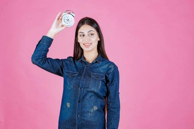 Mujer joven en camisa de mezclilla sosteniendo y promocionando un despertador