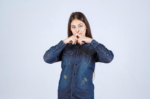 Mujer joven en camisa de mezclilla tratando de prevenir y detener algo