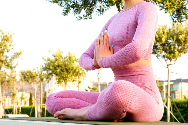 Mujer joven en camisa morada y pantalones en la hierba durante el día dentro del parque verde meditando y haciendo yoga en diferentes poses