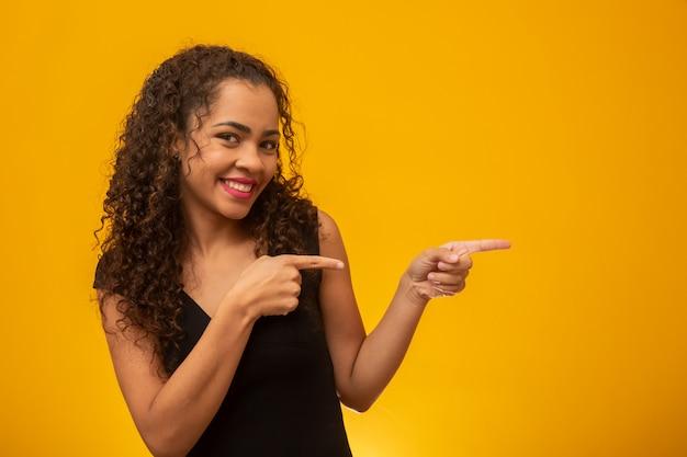 Mujer joven con camisa negra apuntando hacia un lado con un dedo para presentar un producto