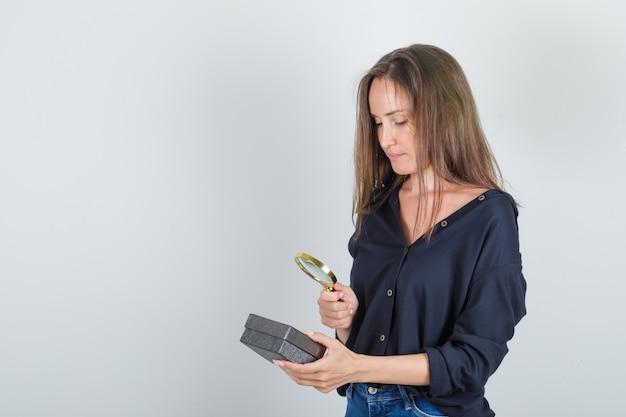 Mujer joven en camisa negra, pantalones cortos de jeans mirando caja de reloj a través de lupa