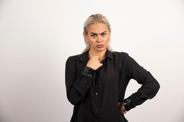 Mujer joven en camisa negra posando sobre fondo blanco. foto de alta calidad