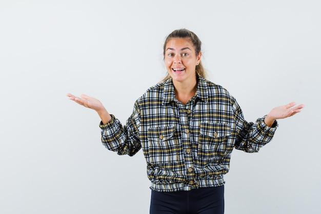 Mujer joven en camisa, pantalones cortos haciendo gesto de escamas y mirando feliz, vista frontal.