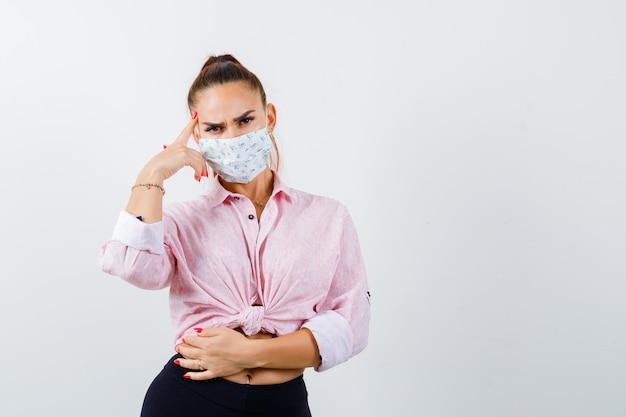 Mujer joven en camisa, pantalones, máscara médica de pie en pose de pensamiento y mirando pensativo, vista frontal.