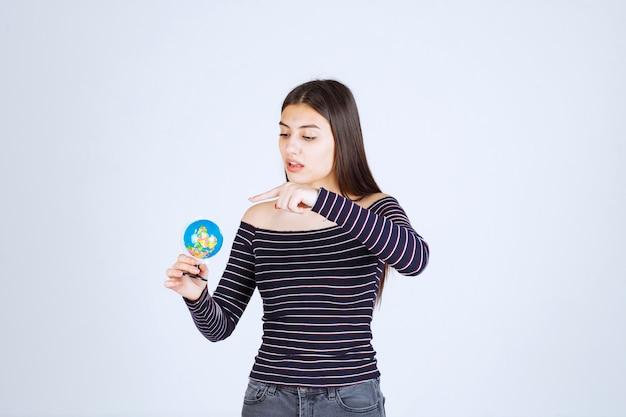 Mujer joven en camisa a rayas sosteniendo un mini globo y adivinando un lugar sobre él