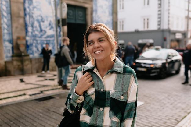 Mujer joven con camisa vaquera caminando por la calle de la ciudad