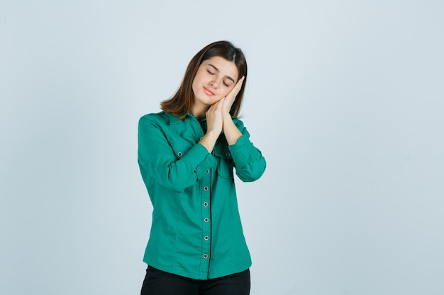 Mujer joven en camisa verde apoyado en las palmas de las manos como almohada y mirando pacífica, vista frontal.
