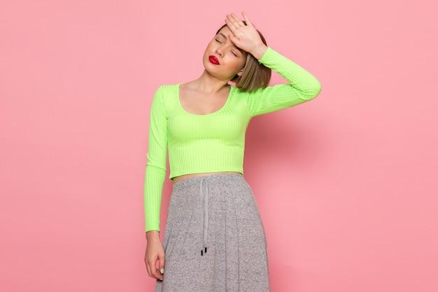 Mujer joven en camisa verde y falda gris posando con expresión cansada