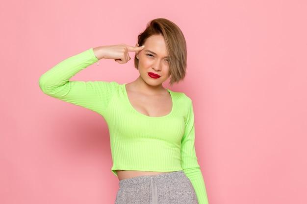Mujer joven con camisa verde y falda gris tocando su cabeza con expresión enojada