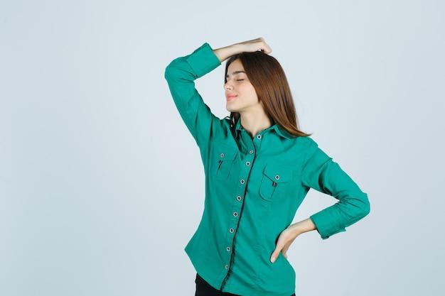 Mujer joven en camisa verde sosteniendo la mano en la cabeza y mirando relajado, vista frontal.