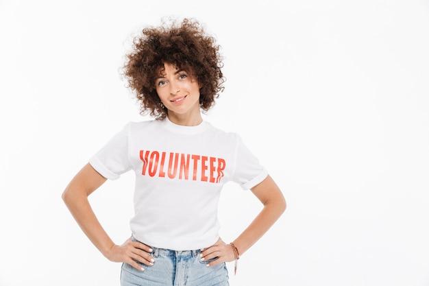 Mujer joven en camisa voluntaria de pie con las manos en las caderas