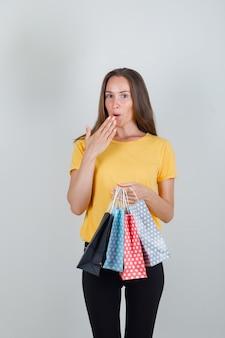 Mujer joven en camiseta amarilla, pantalón negro sosteniendo bolsas de papel y mirando sorprendido