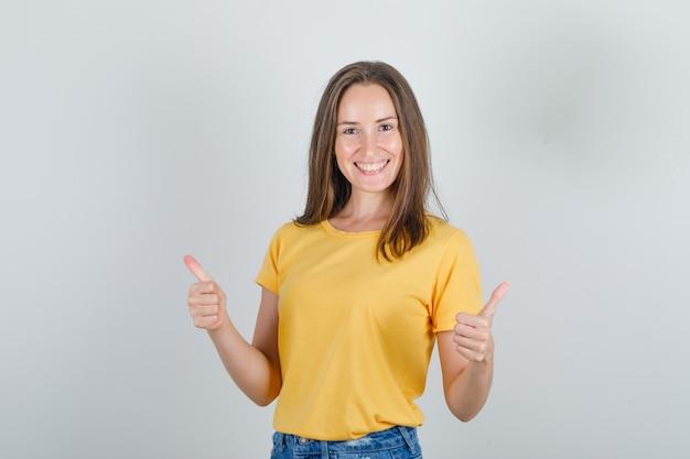 Mujer joven en camiseta amarilla, pantalones cortos mostrando los pulgares hacia arriba y mirando feliz