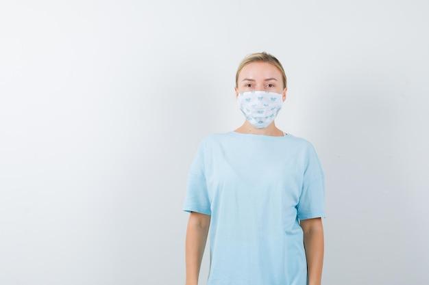 Mujer joven en una camiseta azul con una máscara médica
