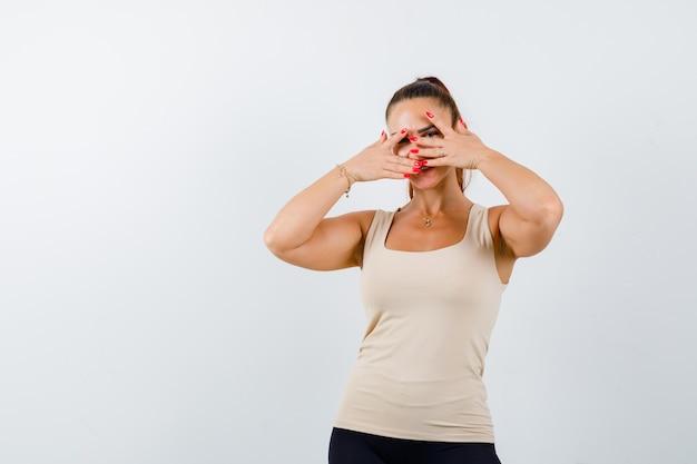 Mujer joven en camiseta beige mirando a través de los dedos y mirando linda vista frontal.