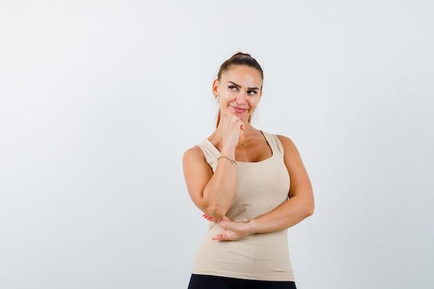 Mujer joven en camiseta beige de pie en pose de pensamiento y mirando bonita, vista frontal.