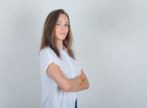 Mujer joven en camiseta blanca, jeans de pie con los brazos cruzados y mirando alegre.