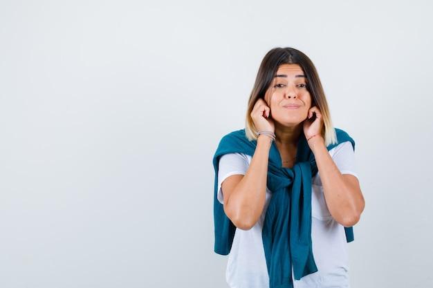 Mujer joven en camiseta blanca con las manos cerca de las mejillas y mirando pensativo, vista frontal.