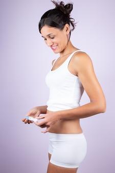 Mujer joven en camiseta blanca y pantalones cortos, con prueba de embarazo
