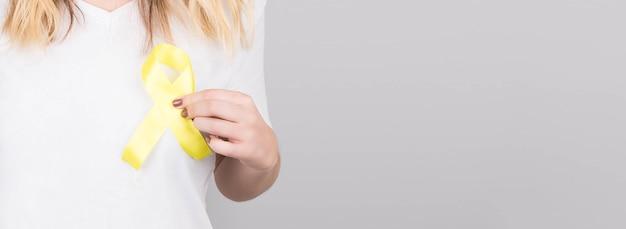 Mujer joven en camiseta blanca con símbolo de conciencia de cinta amarilla para el suicidio