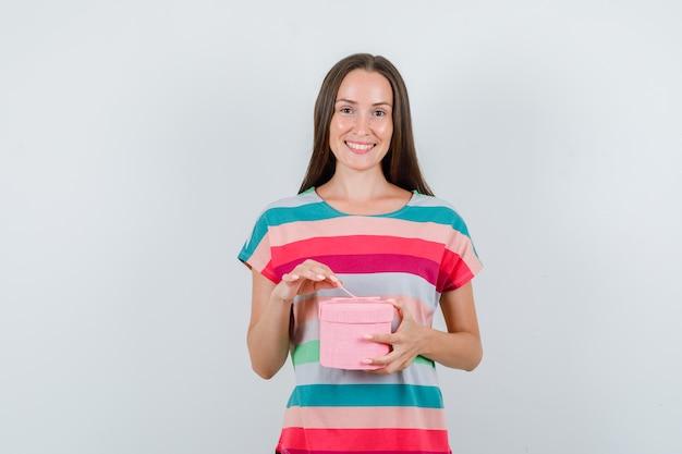 Mujer joven en camiseta con caja de regalo y mirando contento, vista frontal.