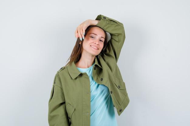 Mujer joven en camiseta, chaqueta posando con la mano levantada en la cabeza y mirando alegre, vista frontal.