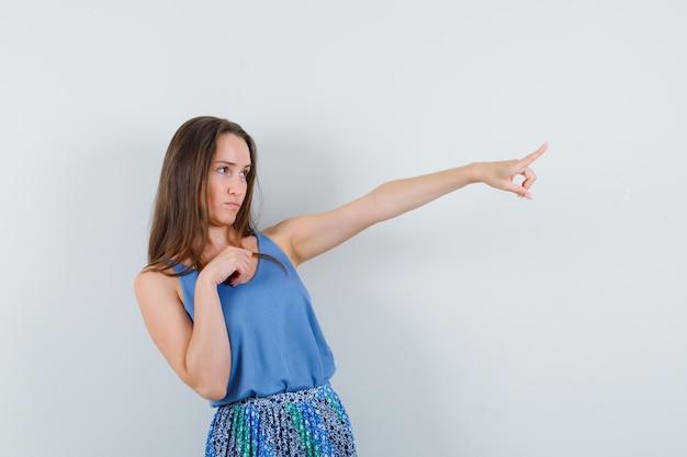 Mujer joven en camiseta, falda apuntando hacia afuera y mirando enfocado, vista frontal.