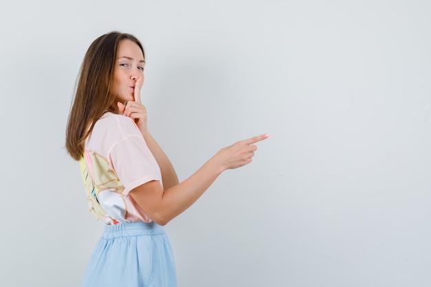Mujer joven en camiseta, falda apuntando a algo con gesto de silencio.