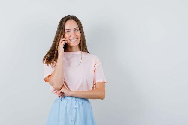 Mujer joven en camiseta, falda hablando por teléfono móvil y mirando alegre, vista frontal.