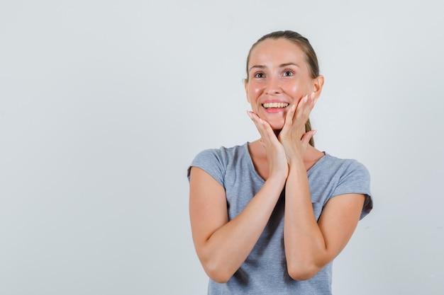 Mujer joven en camiseta gris tocando la barbilla y mirando alegre, vista frontal.