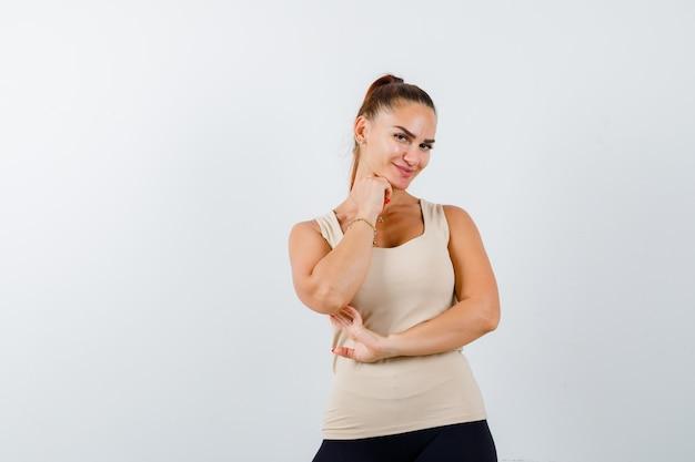 Mujer joven en camiseta sin mangas beige sosteniendo la mano debajo de la barbilla y mirando linda, vista frontal.