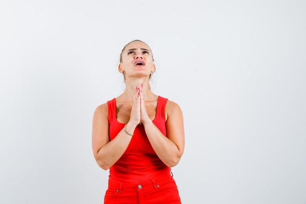 Mujer joven en camiseta sin mangas roja, pantalones mostrando gesto de namaste y mirando preocupado, vista frontal.