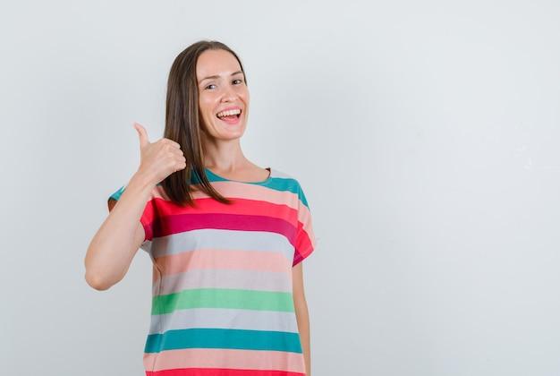 Mujer joven en camiseta mostrando el pulgar hacia arriba y mirando feliz, vista frontal.