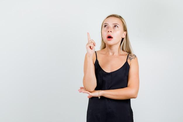 Mujer joven en camiseta negra apuntando hacia arriba con el dedo y mirando enfocado